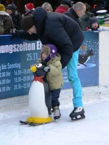 Who's supporting who? Dad and son skating at a Christmas market near the Alexanderplatz